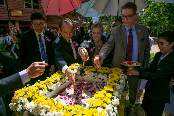 USAID Program Office Director Steven Majors, second from right, lays flowers on the cornerstone for a new hospital in Sangkhlaburi.