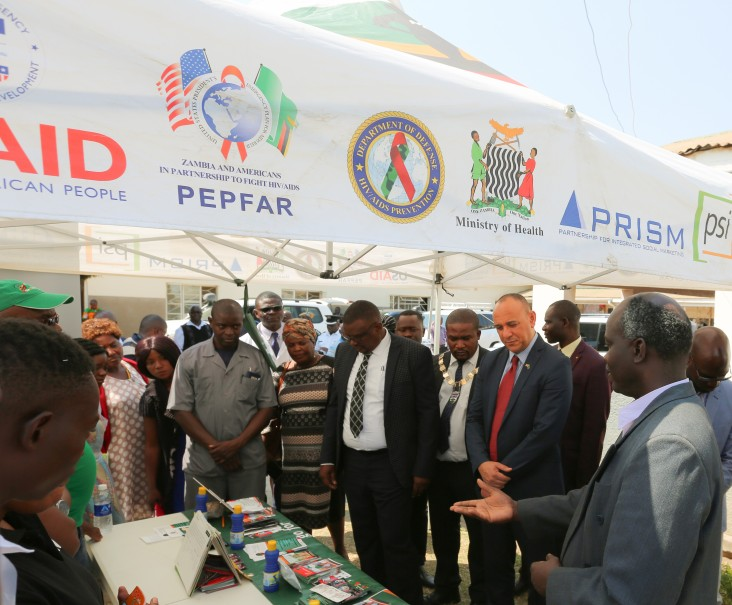 Chargé d'affaires Martin Dale (center right) visits a Ministry of Health's booth after officially handing over the nineteen solar-power systems to the Ministry of Health.