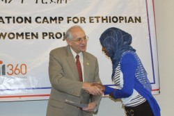 U.S. Ambassador Donald Booth presents a completion certificate to one of the 167 first-year female students.
