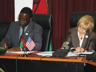 Malawi's Minister of Finance Dr. Ken Lipenga and U.S. Ambassador to Malawi Jeanine Jackson sign bilateral assistance agreements.