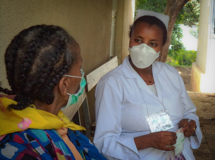 A health care worker checks up on a patient with TB.