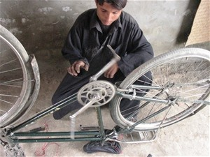 Ashraf Khan fixes a bicycle in his shop, which he opened after completing a USAID-funded bicycle repair course. The shop provide