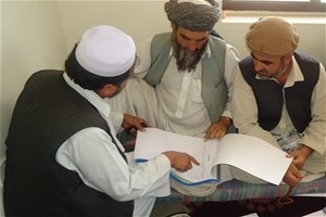 USAID field personnel distribute and demonstrate how to use the new decision letter booklets with village elders in Surkhrod Dis