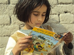 A school girl reads a USAID information comic book about the illegal use of the traditional conflict resolution practice of Baad