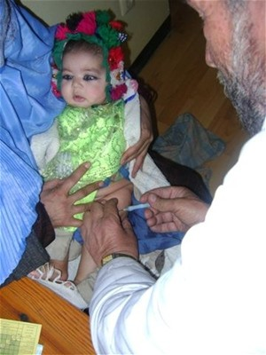 An Afghan doctor administers a vaccination to a baby girl in Farza District to protect her from communicable diseases.