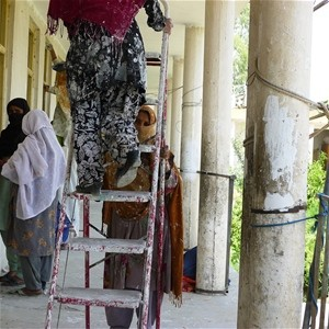 Women painting and plastering a veranda at a girls's school on the outskirts of Jalalabad.