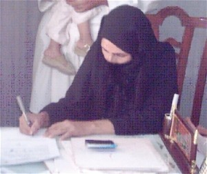 Mrs. Laila of Kandahar Province signs the papers legally freeing her from marriage after her husband's death eight years before.