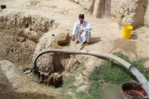 Abdul Manan and the water pump provided to him by USAID's ACAP program.