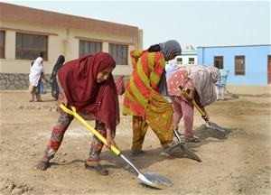 Women from Lashkar Gah work in scorching summer heat to rehabilitate a women's high school.