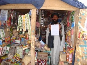 Beneficiary Abdul (right) in the grocery shop he set up with USAID assistance.