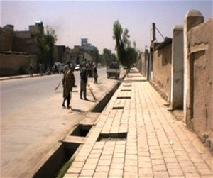 Workers put the final touches on a sidewalk in Kandahar. The city government initiated what became a very successful public work