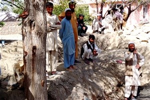 Laborers pause while excavating a damaged section of canal that runs through the Khas Kunar district center.