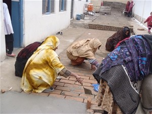 Women laying bricks for a school sidewalk. From masonry to carpentry, the school repair projects have served as effective traini