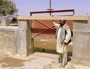 Paktika Province farmer, Haji Lal Khan, stands at a water gate connecting the Paltu River intake with the Sra Kala can-al.