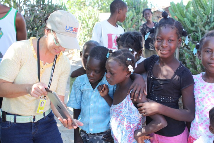 USAID/Haiti GIS Specialist Anna Brenes shows local children photos of the nearby road she mapped.