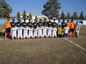 Soccer teams from two different parts of Helmand province pose for a 'family' photo after playing each other