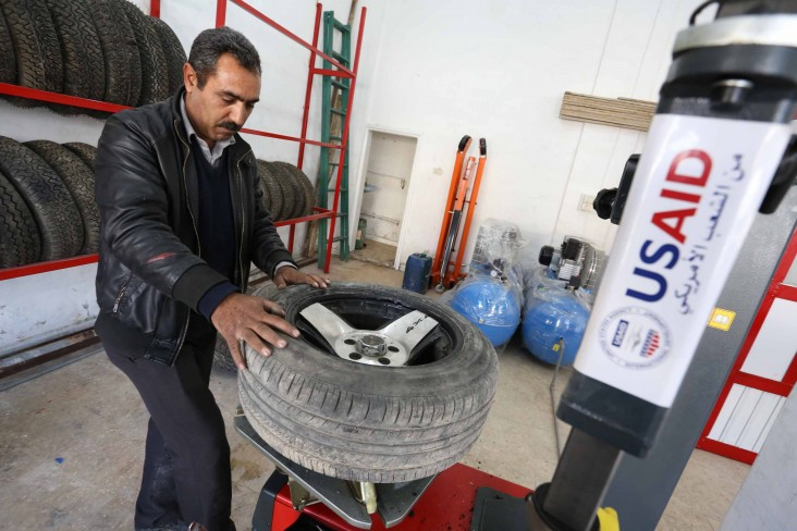 Abdullah Sharari, owner of a tire fixing station in Irbid, stands behind a tire changing machine in his new shop