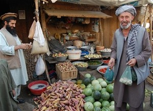 Baharak Bazaar vegetable trader Faiz Mohammad (left) has enjoyed brisk sales since the completion of USAID's road building campa