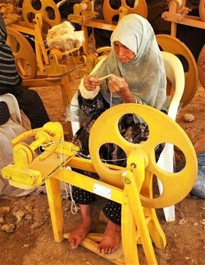 An Afghan woman uses a foot-treadle spinning wheel that has boosted her productivity and helped to provide jobs for other local