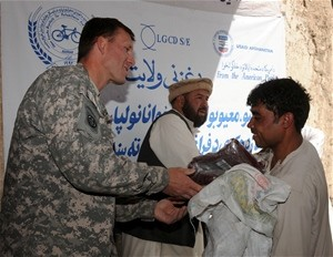 Ghazni PRT Commander Lt. Colonel Wilson Marks and National Disabled Association Director Fazel Haq Sadat Mosa hand a new set of