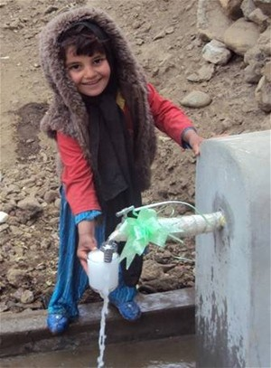 A new piped water system fulfills a basic need for residents. Here a young girl collects a glass of drinking water from newly co