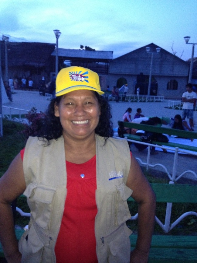 Maria Tereza Sangama wears a hat bearing the campaign slogan: Pure Collective Energy!
