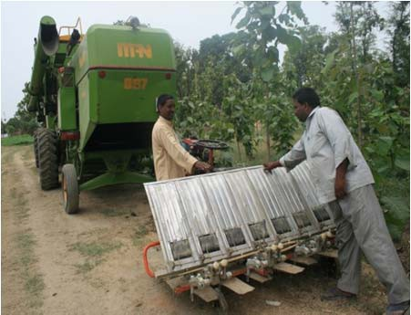 Ramavadh Chaudhary shows a farmer how to operate a mechanical rice transplanter.