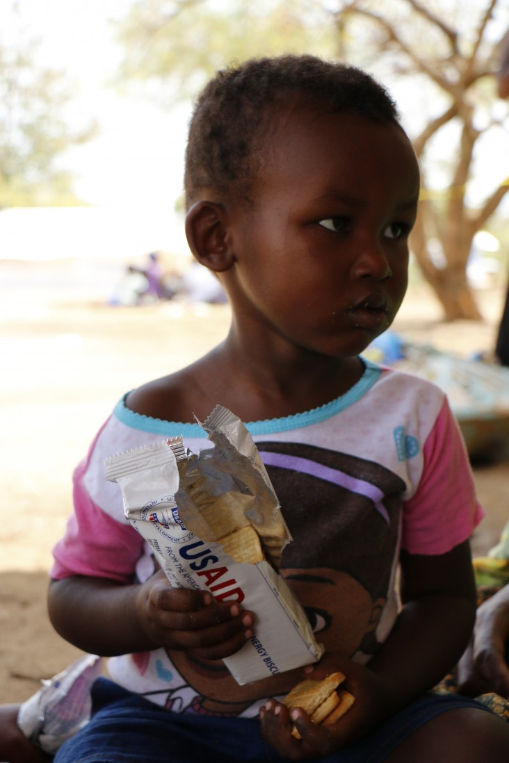Robert, 2, eats high-energy biscuits after arriving in Uganda