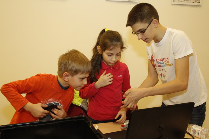 Andrei Copaci mentoring two kids to set up a robot at EU Robotics Demo Day event