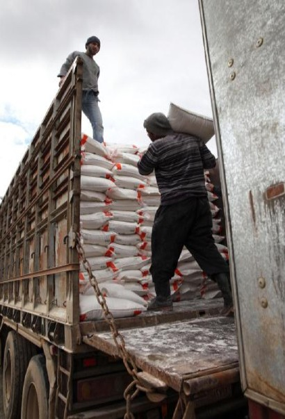 Workers load newly-milled flour onto a truck in Syria