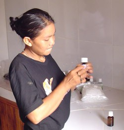A young woman of the Uru-eu-wau-wau tribe bottles and labels copaiba oil.