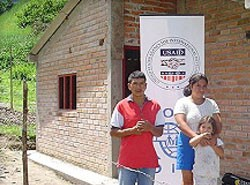 Flor and José Baca pose in front of their new home in Los Andes de Sotomayor, Nariño, which USAID helped them build with their o