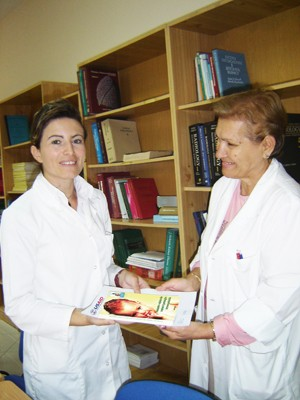 Sadeta Noka (left) receives the new pediatric Clinical Practice Guidelines from Margarita Rumano