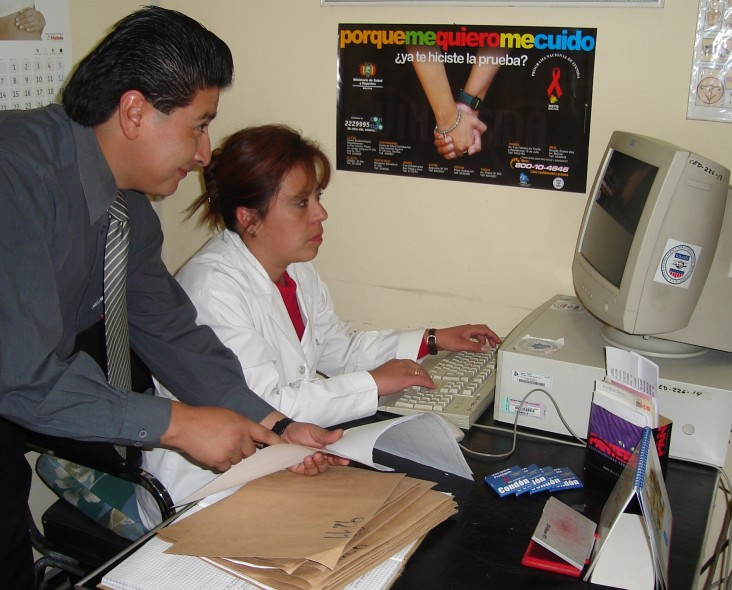 Dr. Percy Calderon, left, assists a La Paz health worker in analyzing HIV/AIDS trends using a new automated reporting system in