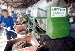 Workers from Luntiang Nasugbu Multipurpose Cooperative produce fertilizer at the CADP composting facility.