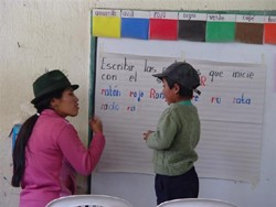 Florida Ante, a USAID-trained teacher, shows a student how to write at her school near La Vaquería, Ecuador.