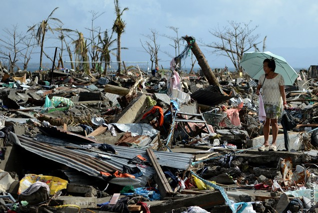 A survivor walks among the debris of houses destroyed by Super Typhoon Haiyan in Tacloban in the eastern Philippine island of Le