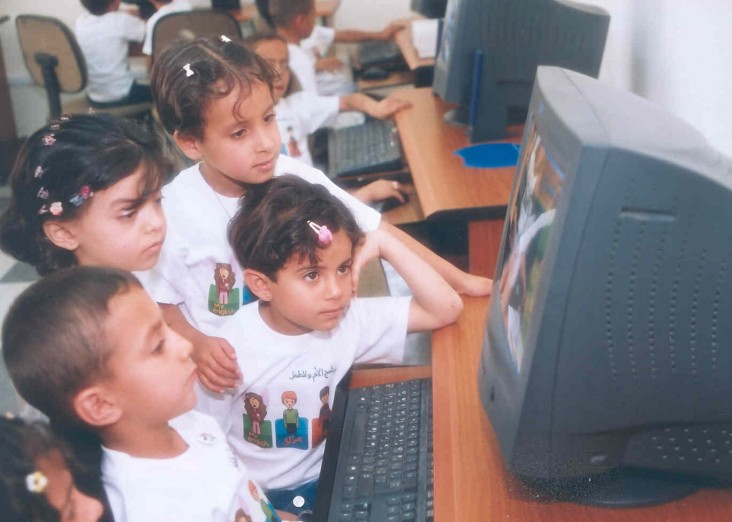 Children are captivated by the educational software program at a knowledge station in Madaba, a town south of Amman, Jordan.