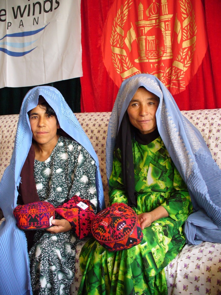 Members of a silkwork production program in northern Afghanistan display their silk- embroidered handiwork.