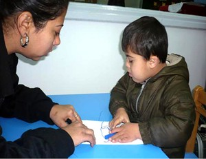 George and his mother work together on specialized learning activities at the Caritas center.