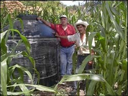 José Pérez (right) shows visitors the water storage tank he installed on his farm.