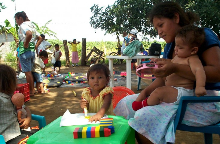 Families meet at a rural children's center to monitor their children's development and receive complementary food.