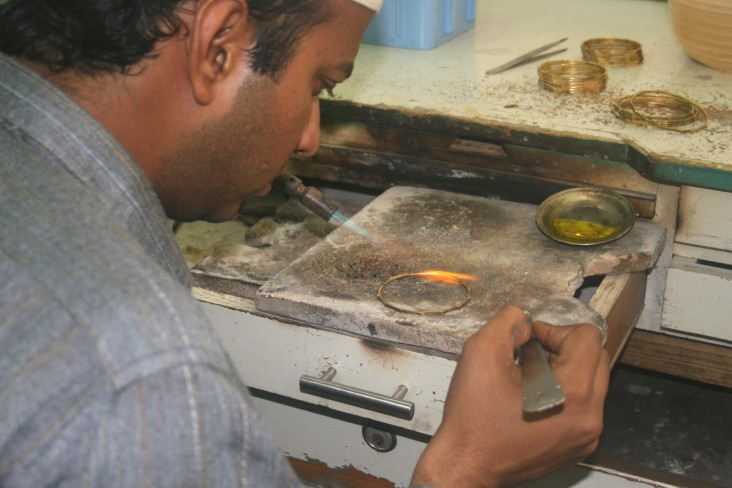 An artisan in a Karachi workshop solders gold bangles with a gas flame.