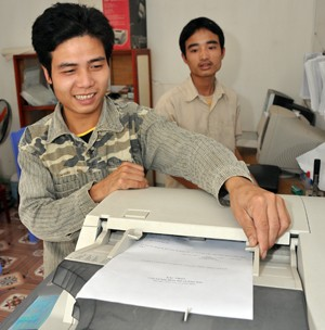 Dang Van Toan, left, operates the new photocopy machine in his computer services and copy shop in Me.