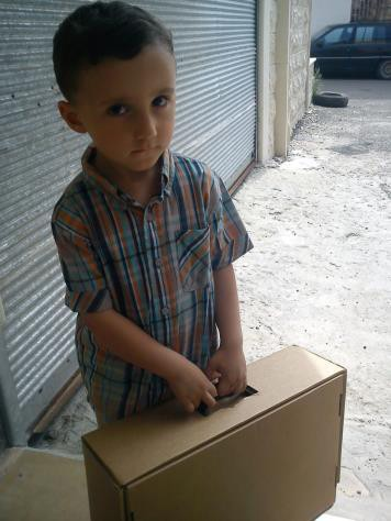 A young Syrian boy receives a box of clothing at a USAID-supported distribution site.