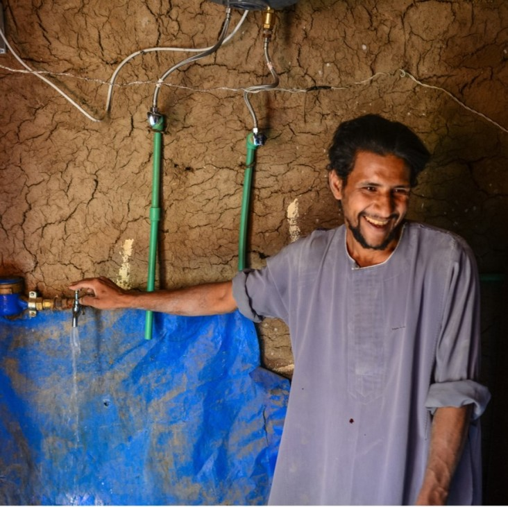 A resident of Upper Egypt getting potable water from a faucet