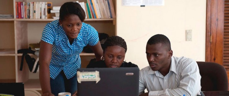 ENDK journalist Witza Petit Antoine is flanked by Internews researchers Louisena Louis, left, and Franck Lafont as they sort SMS