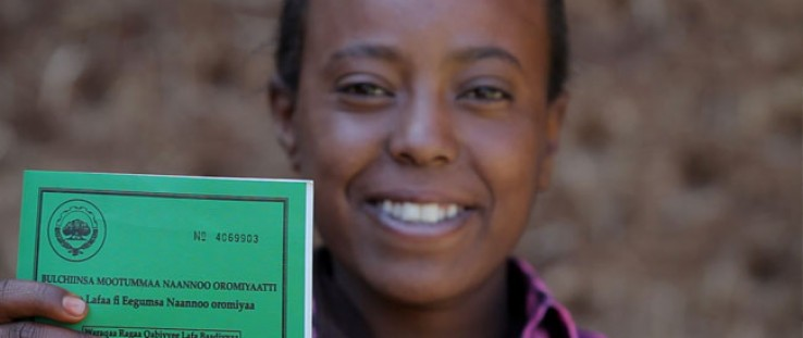 Asilya Gemmal, 14, of Gure Tebeno Union, proudly displays her land certificate obtained from the Ethiopian Government with USAID