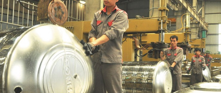 Employees at the Sonha Corporation produce stainless steel water tanks in Hanoi.