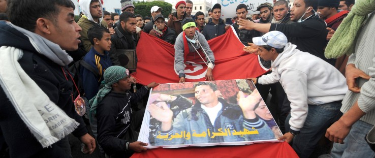 Tunisians from the Kasserine region walk with a Mohammed Bouazizi poster and the national flag in front of the government palace